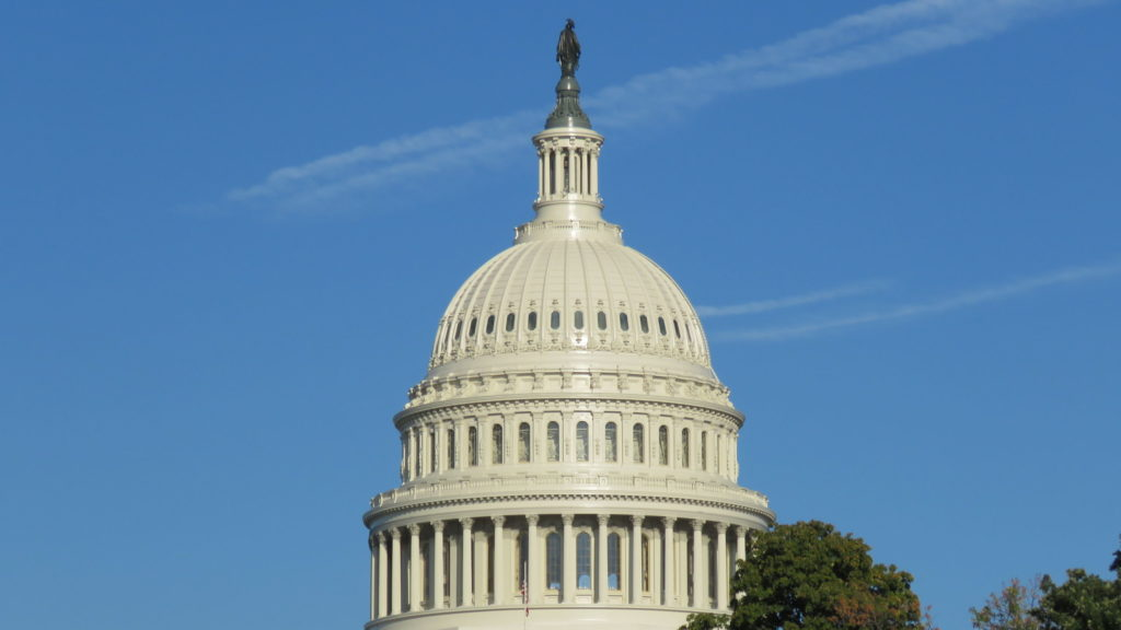Image of the Dome of the US Capitol Building against a blue sky.